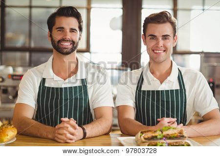 Portrait of two smiling baristas at the coffee shop