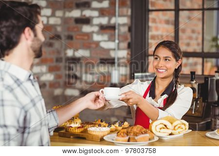 Smiling waitress serving a client at the coffee shop