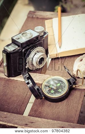 Compass Notepad And Camera On Wooden Background