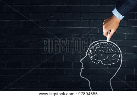 Human hand drawing brain on black chalkboard