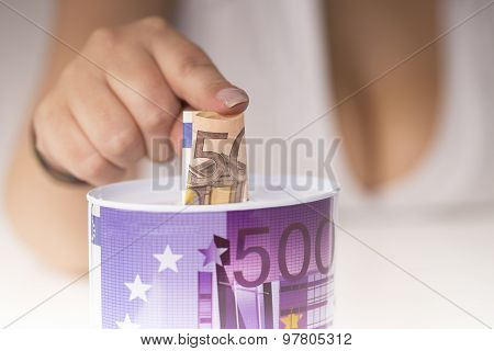 girl with large breasts put a banknote in the piggy bank