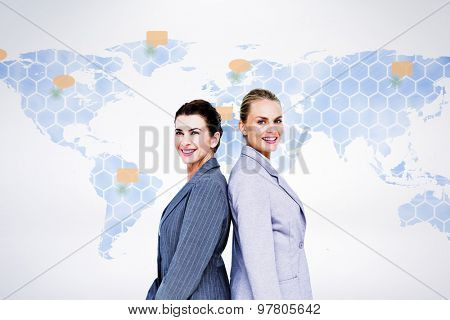 Attractive businesswomen standing back-to-back against world map