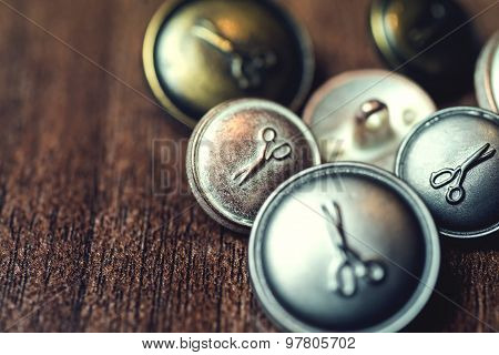 Vintage metal buttons with scissors on it