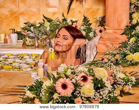 Woman relaxing at flower water spa. Luxury bathroom.