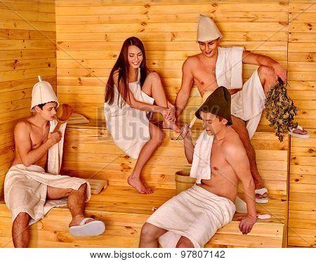 Group people in Santa hat  relaxing at sauna.
