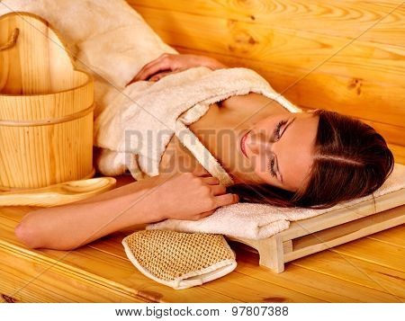Young woman lying on back in sauna. Healthy lifestyle.