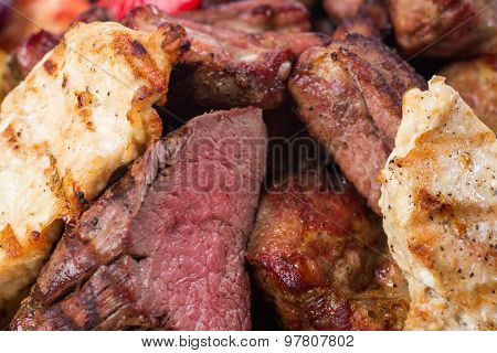 Different kind of grilled meat with sauces on wooden plate.