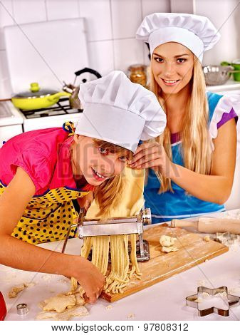 Mother and teen daughter making homemade pasta at kitchen.