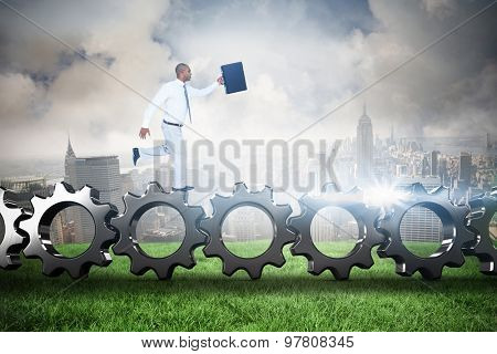 Businessman running with briefcase against cloudy sky over city
