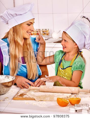 Mother and little daughter baking cookies.