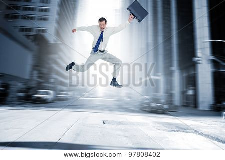 Cheerful jumping businessman with his suitcase against new york street