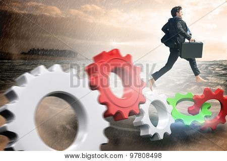 Businessman jumping against stormy sea with lighthouse