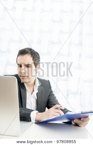 Serious Businessman Filling Documents Or Application At His Worktable While Looking At His Laptop.
