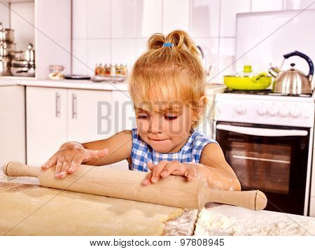 Child without parent with rolling-pin dough at kitchen.