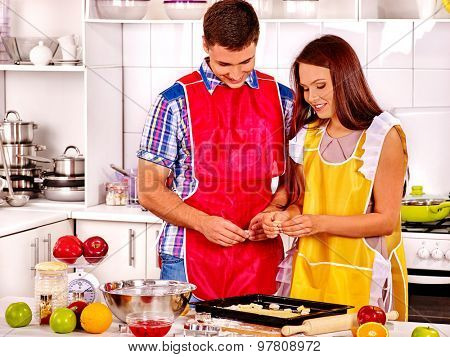 Young happy family looking down and cooking at kitchen.
