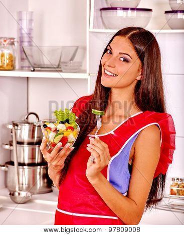 Happy woman eating fresh green salad at kitchen.