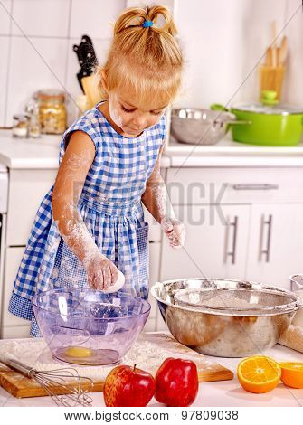 Child with big bowl  dough at kitchen.