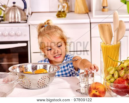 Child with colander cooking dough at home kitchen.