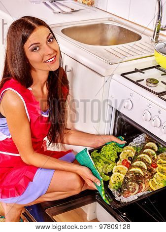 Happy woman prepare fish at oven-tray at home kitchen.