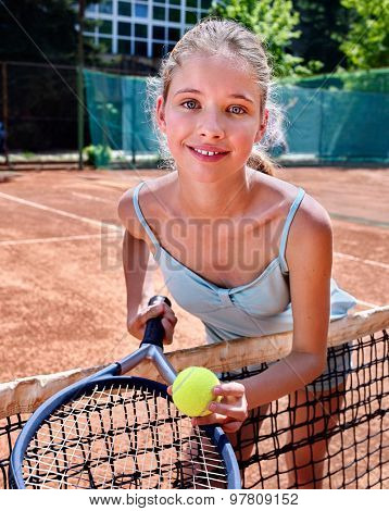 Sport kids girl with racket and ball looking at camera on  brown tennis court.