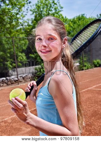 Teenager girl holding  racket and ball on  brown tennis court.
