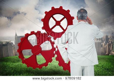 Thinking businessman against cloudy sky over city