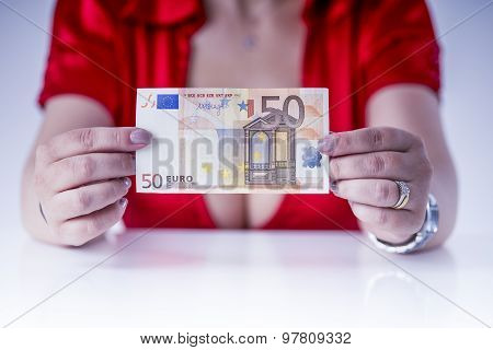 girl with large breasts shows a banknote