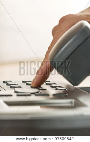 Closeup Of A Male Hand Making A Phone Call By Dialing A Classical Landline Telephone