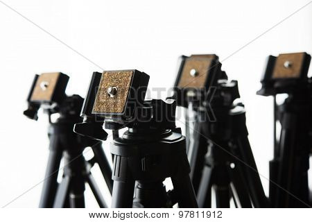Multiple camera tripods ready for filming or photo session. Photography or filming equipment.