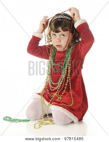 An adorable, dressed up preschooler, worriedly looking up as she's putting strands of Christmas beads around her neck.  On a white background,.