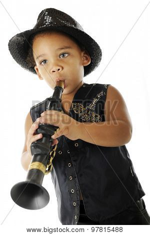 An adorable preschooler playing a toy clarinet in his sparkly fedora and black leather jacket.  On a white background.
