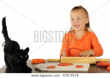 A pretty preschooler happily cutting Halloween decorations from modeling clay.  A scary black cat sits near her working space.
