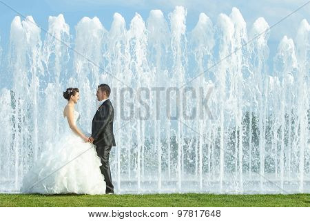 Bride And Groom Holding Hands In Front Of Water Fountain
