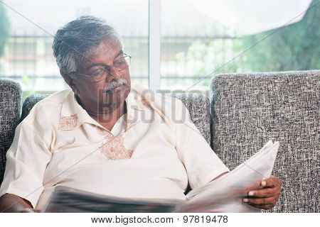 Senior Indian man reading newspaper at home. Asian old people living lifestyle indoors.