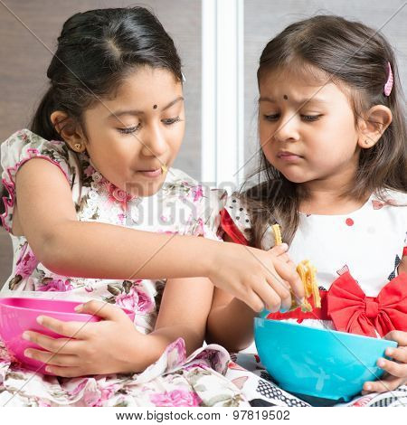 Indian girls sharing food, traditional snack murukku with each other. Asian sibling or children living lifestyle at home.