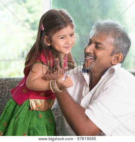 Indian father playing with daughter at home. Asian family indoors living lifestyle.