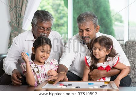 Happy multi generations Asian Indian family playing carrom game at home. Grandparent, parent and children indoor lifestyle.