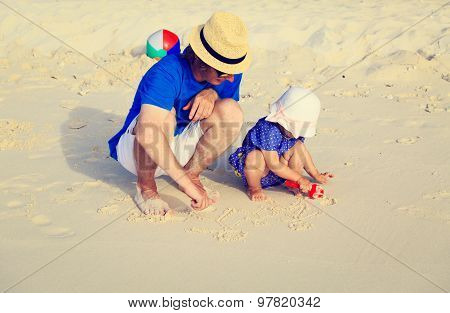 father and little daugther drawing family picture on beach