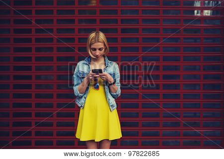 Female student in the dress using mobile phone for connect to wireless while standing outdoors