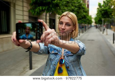 Beautiful young woman making self portrait with a cell phone camera while enjoying a day