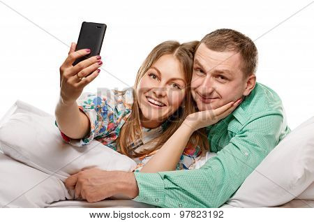 Happy couple with smartphone taking selfie