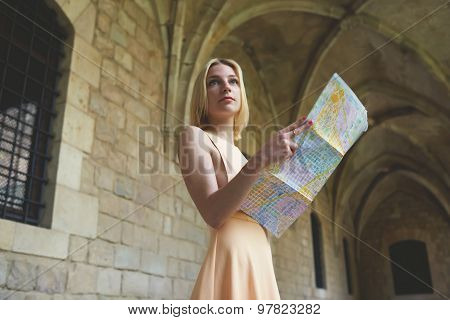 Portrait of stylish hipster female studying a map while standing in antique town in summer