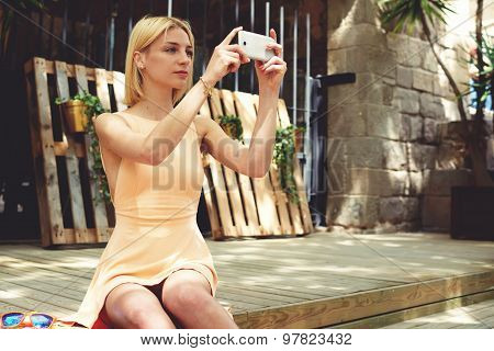 Female tourist taking picture with her smart phone while sitting outdoors at beautiful sunny day