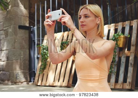 Lovely young woman in dress photographing urban view with mobile phone camera during summer journey