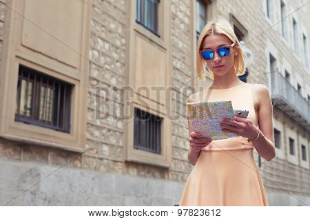 Portrait of young female tourist checking out the sights while reading a map in urban setting