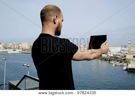 Young handsome man photographing marina port city with touch pad while enjoying vacation journey