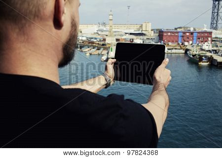 Male tourist with digital tablet camera taking picture of beautiful city from viewpoint