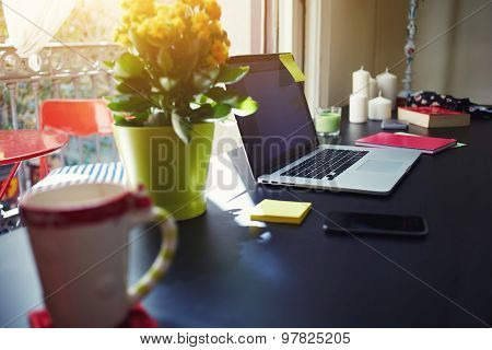 Side view modern table with with open laptop computer, smartphone and pot of flowers