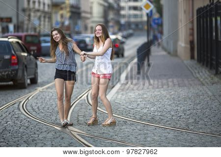Funny teenage girls together walking on the pavement on the street.