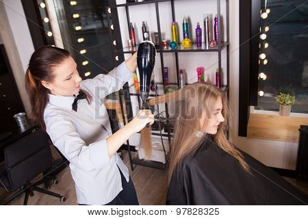 Hairstylist Drying Hair Blonde in Salon